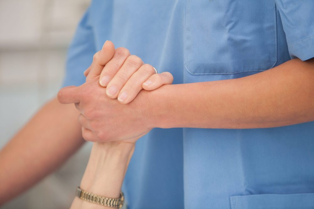 Nurse holding the hands and take care of the elderly woman